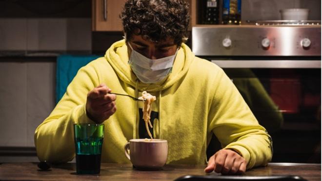 ragazzo cn mascherina che mangia da una tazza