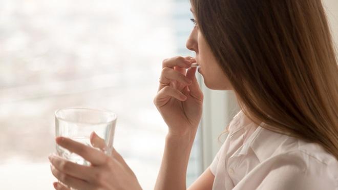 donna con bicchiere d'acqua in mano che prende un farmaco