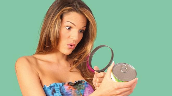 donna con lente di ingrandimento che guarda un'etichetta