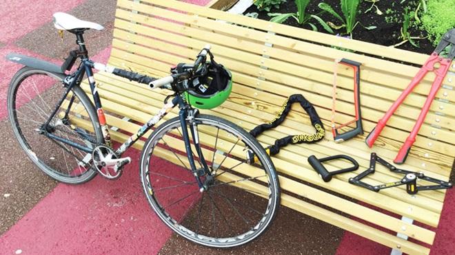 bici chiusa con catena e lucchetto appoggiata a una panchina