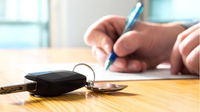 primo piano chiave auto e mano che firma