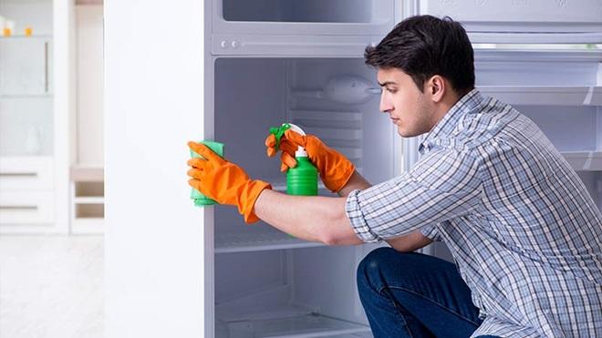 uomo che pulisce frigorifero