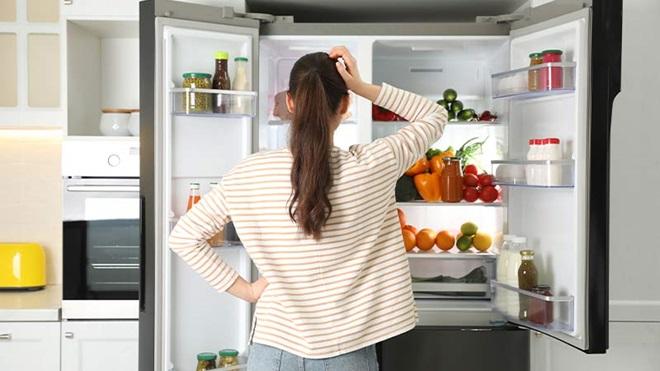 donna porta la mano alla fronte davanti a frigorifero aperto