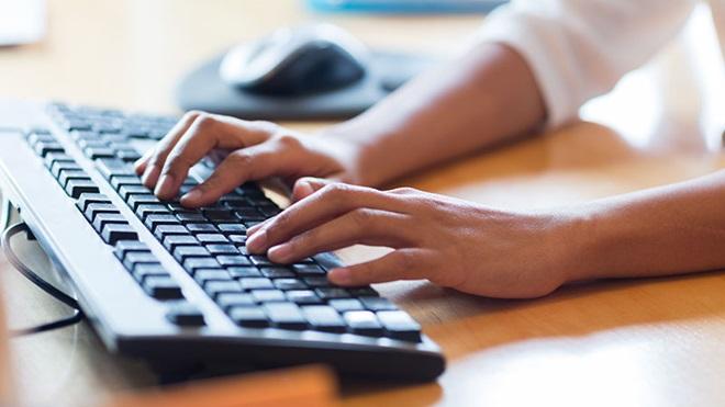 mani che utilizzano una tastiera esterna pc