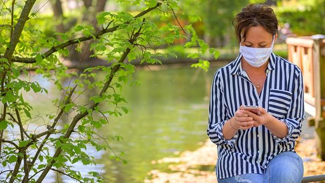 donna con nascherina che guarda smartphone