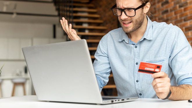 uomo davanti a PC con carta di credito in mano