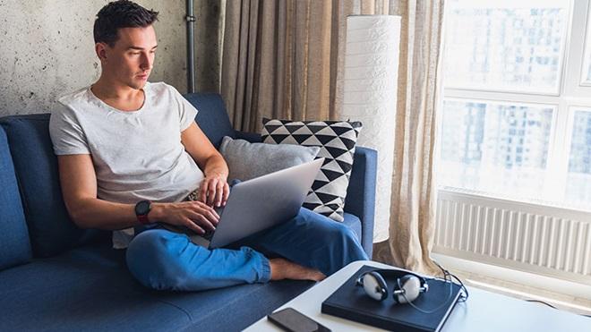 ragazzo seduto sul divano con PC sulle gambe