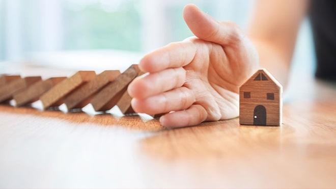 mano protegge casetta di legno